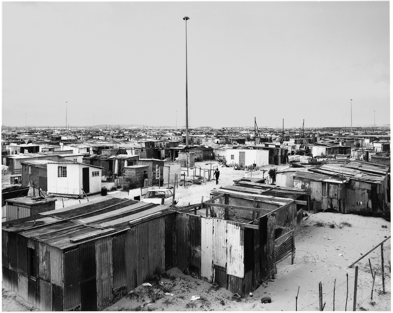 David Goldblatt. Structures: Flushing Meadows – so called because it had water-borne sanitation – and lighting masts, Site B, Khayelitsha, Cape Town, Cape. 11. October 1987, 1987. Series: Structures. Courtesy The Walther Collection and Goodman Gallery, Johannesburg.